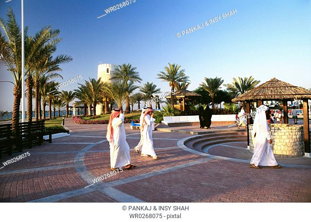 Small group of people enjoying the peaceful environment at a place surrounded with palm trees