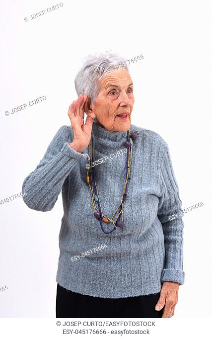 senior woman putting a hand on her ear because she can not hear on white background