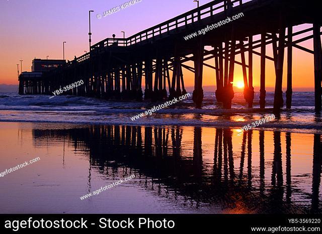 The sun sets behind the Newport Beach pier in California