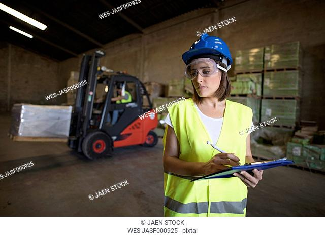 Woman is taking stock in warehouse of construction company