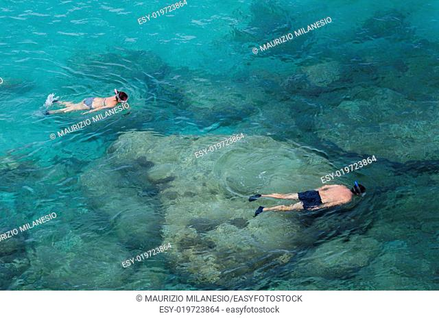 Two people do snorkeling near the rocks in a wonderful blue and green sea
