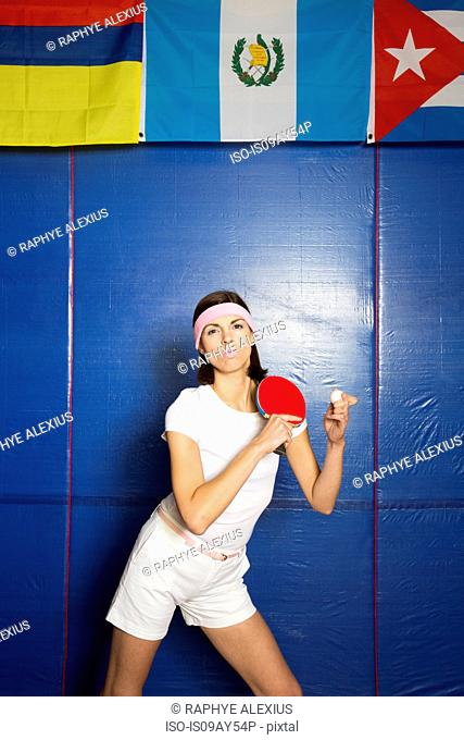 Table tennis player posing with bat and ball