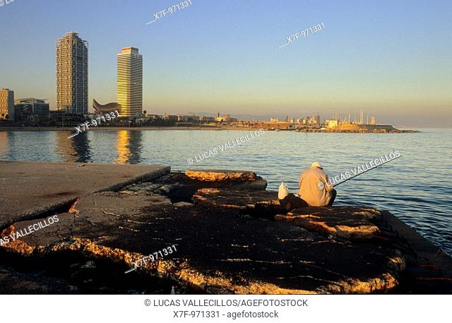 Barcelona: Fisherman in jetty of Gas Barceloneta beach  In background Mapfre tower and Hotel Arts