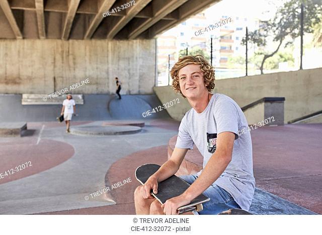 Portrait smiling teenage boy with skateboard at skate park