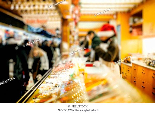 Illuminated Christmas fair kiosk market stall with loads of delicious food - chocolate, pastries, sweets and traditional French Christmas food blur, bokeh