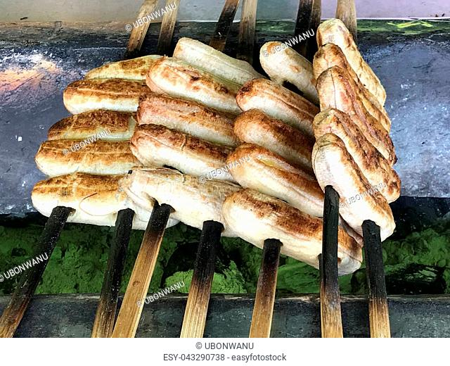 Thai street food, grilled organic banana in wooden stick on hot charcoal stove