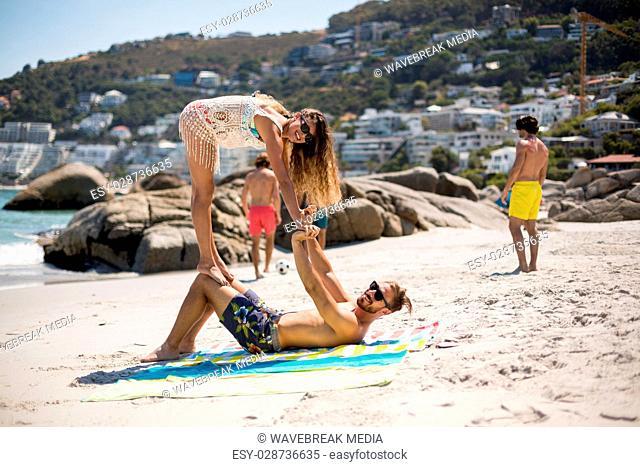 Woman balancing on knees of man at beach