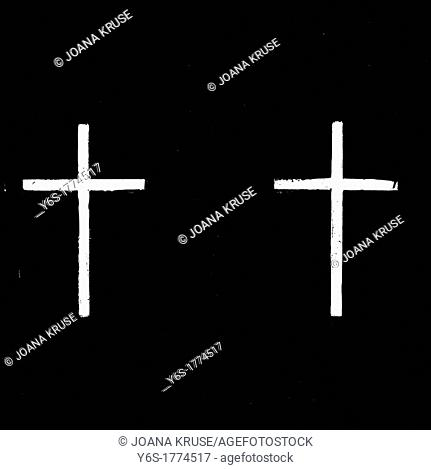 two white, painted crosses on a black background