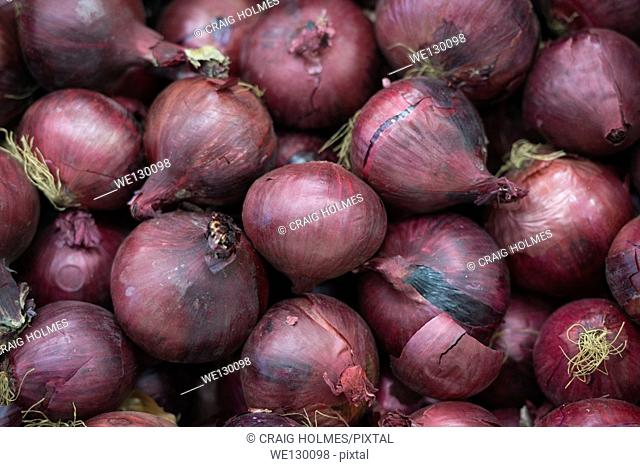 Red onions on display in a supermarket