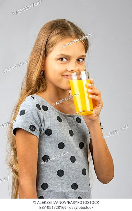 A ten-year-old girl drinks juice, and with a smile looked at the frame