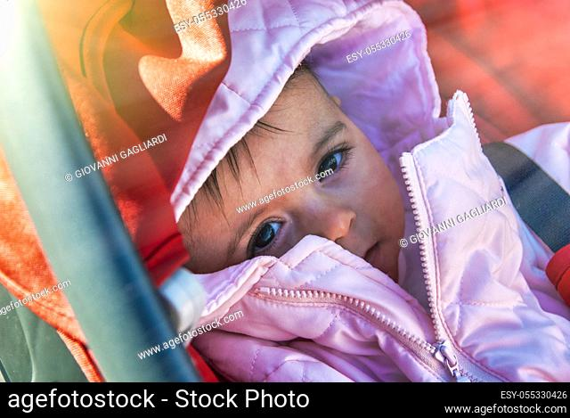 Baby in the cradle ready to sleep. Her body covered in winter clothes