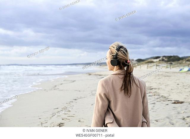 Spain, Menorca, back view of senior woman listening music with wireless headphones on the beach in winter