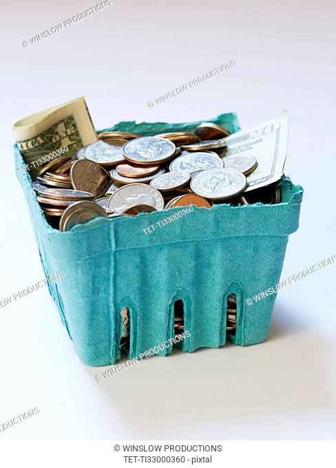 Coins and banknotes in carton box on on white surface