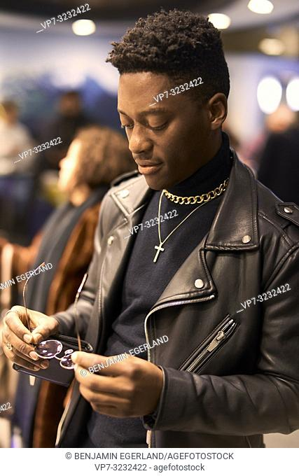 young fashionable man looking at glasses in hands in city between passersby, African descent, in city, Munich, Germany