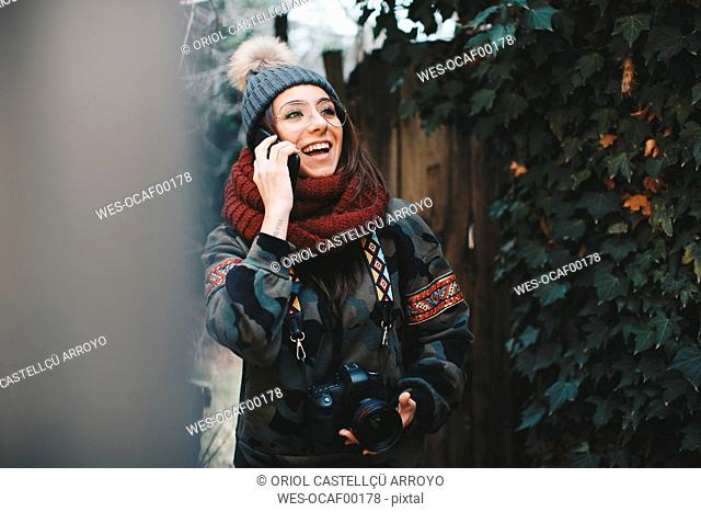 Portrait of laughing young woman with camera on the phone