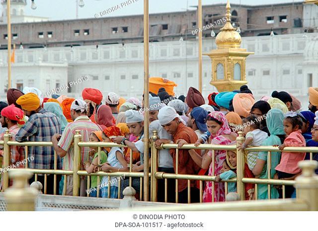 Devotees wait  at gurus bridge which leads to the Harmandir ; Golden temple ; Amritsar ; Punjab ; India