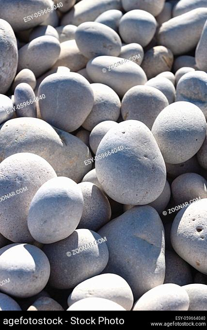 Detail up of bright white and grey stones at a sunny beach