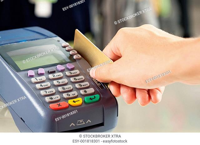 Close-up of payment machine buttons with human hand holding plastic card near by