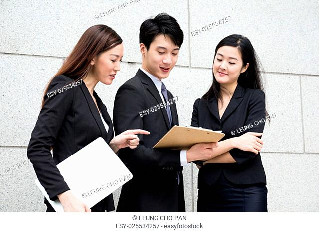 Three business people work together