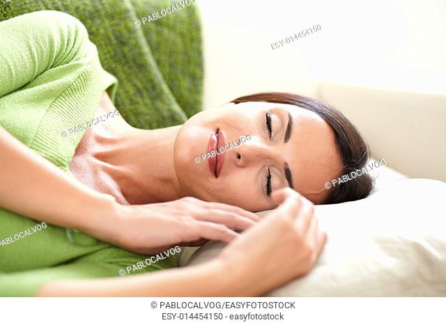 Carefree woman lying on her back and resting indoors with her eyes closed