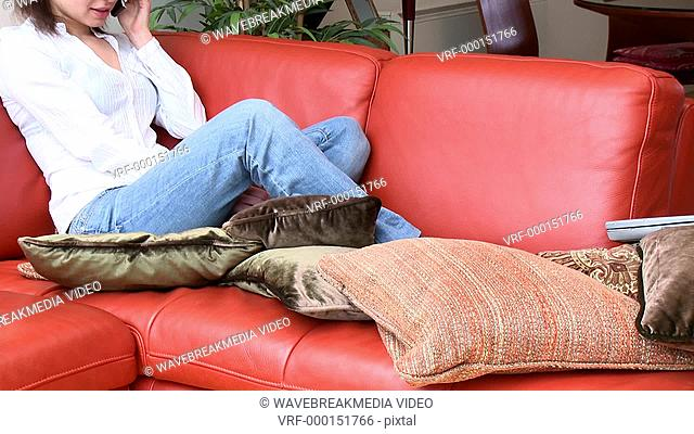 Laughing woman talking on phone sitting on sofa at home