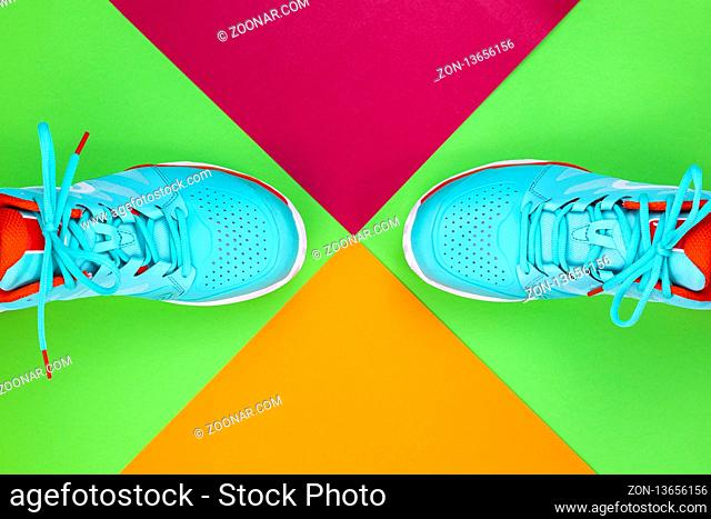 Red, cyan, white pair of new tennis shoes in studio shot over green, pink, purple background. Directly from above