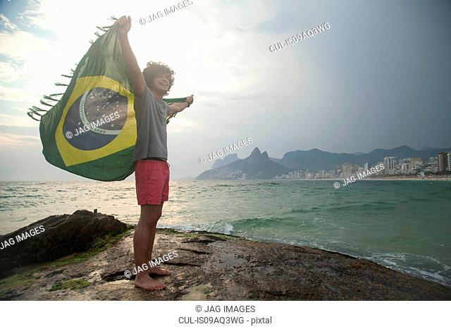 Young man standing on rock holding up Brazilian flag, Ipanema beach, Rio De Janeiro, Brazil
