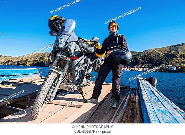 Woman and her touring motorbike on simple ferry crossing Lake Titicaca, Bolivia