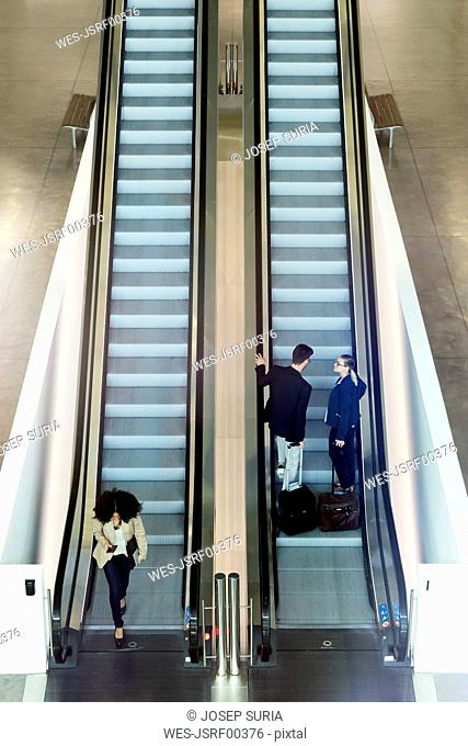 Young business people on an escalator