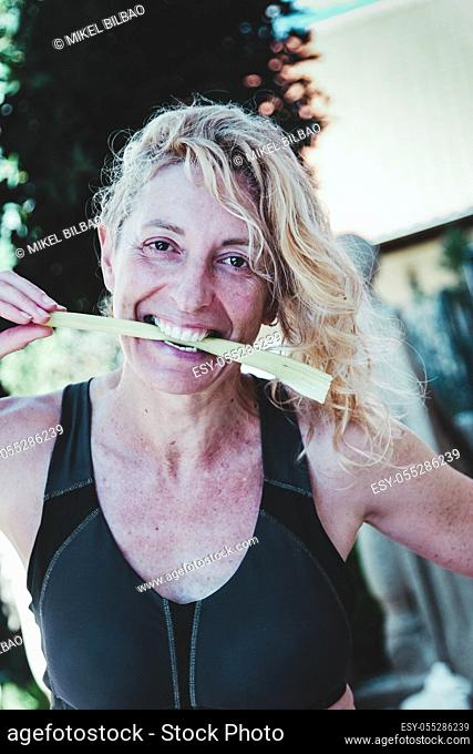 Young mature blonde woman in sportswear beating a celery stem outdoor