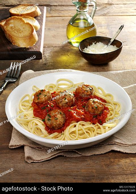 Italian meatballs in tomato sauce on a bed of linguine noodles
