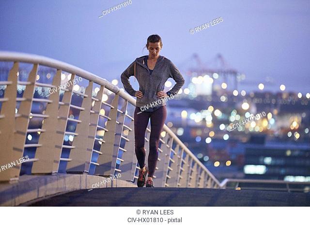 Female runner resting stretching legs on urban footbridge at dawn