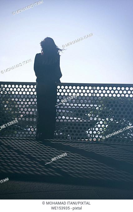 Rear view silhouette of a young woman standing outdoors