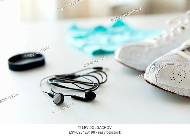 sport, fitness, healthy lifestyle, technology and objects concept - close up of earphones, sports clothing and heart-rate watch on table