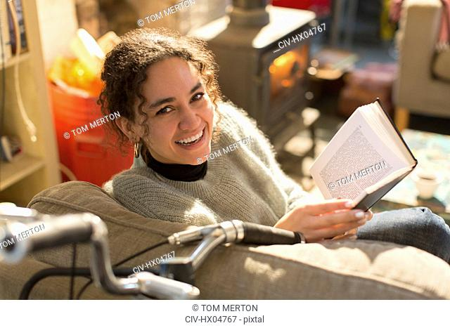 Portrait smiling, happy young woman reading book in armchair