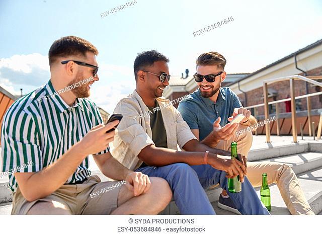 men with smartphones drinking beer on street