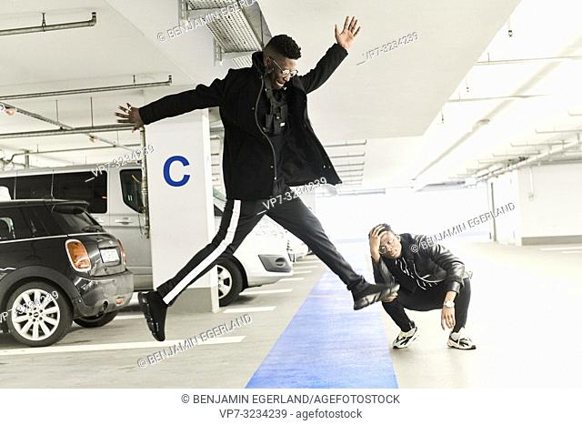 best firends, fashionable, coolness, jumping in car parking space, in Munich, Germany