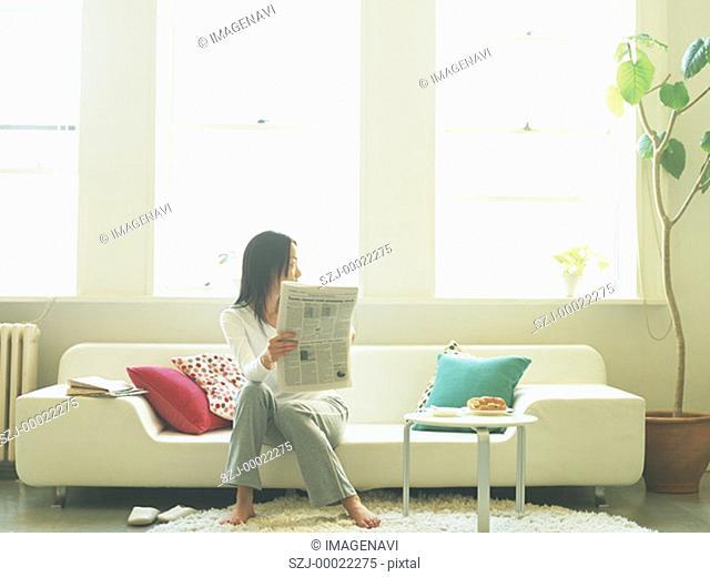 Woman reading newspaper on sofa