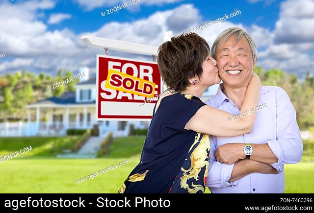 Attractive Affectionate Senior Chinese Couple In Front of Beautiful House and Sold For Sale Real Estate Sign