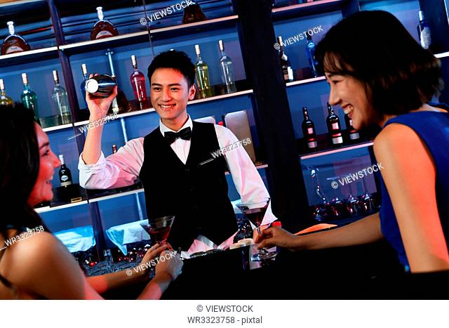 Happy young people drink at the bar