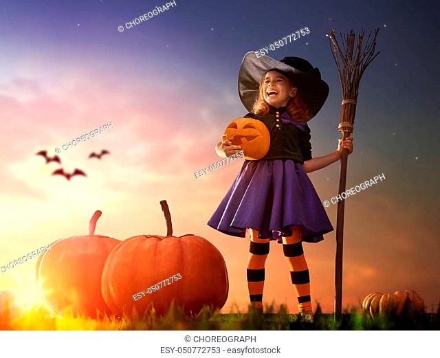 Happy Halloween! Cute little witch with a big pumpkin. Beautiful young child girl in witch costume outdoors