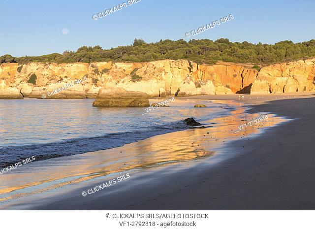 The newly risen sun shines on cliffs and reflected on the beach of Praia do Vau Algarve Faro District Portimao Portugal Europe