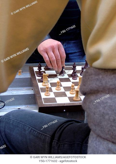 two men playing chess game outdoors