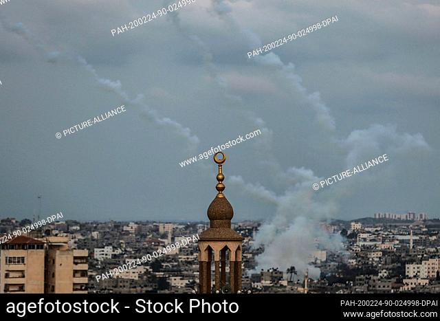 24 February 2020, Palestinian Territories, Gaza City: Rockets leave smoke trails in the sky after being fired from Gaza into the Israeli territories