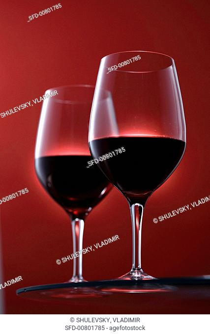 Two glasses of red wine against a red background