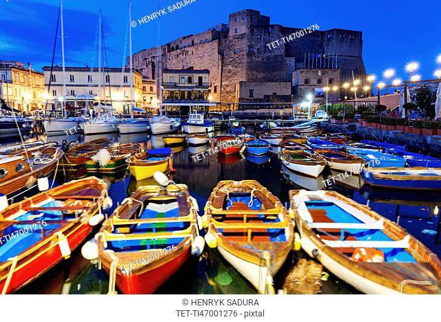Colorful boats and Castel dell' Ovo at night