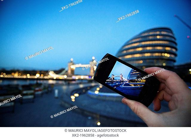Detail of tourist's hand taking pictures of City Hall and Tower bridge with a camera, London, UK
