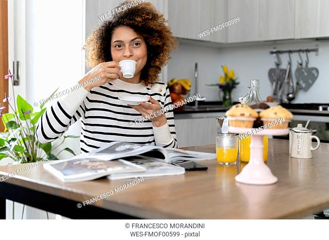 Woman sitting in kitchen, reading magazines and drinking coffee