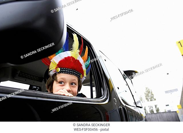 Boy with feather headdress looking out of car window