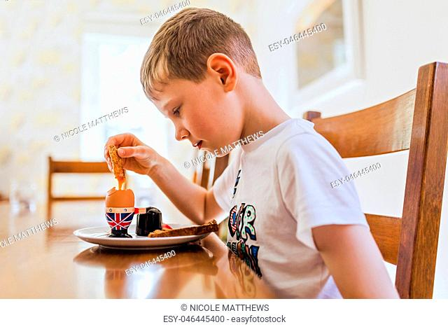 UK, sad boy sitting at breakfast table eating boiled egg